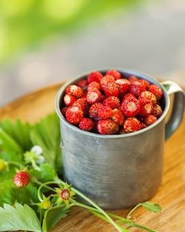 나무 쟁반에 금속 컵에 숲 딸기