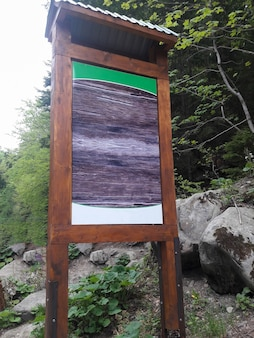 In the forest, there is a large wooden signboard with an empty space for insertion against a background of stones.