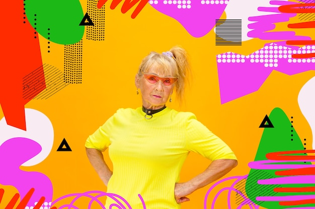 Forever young. portrait of senior hipster woman using devices, gadgets isolated on orange studio background. tech and joyful elderly lifestyle concept. bright, modern illustrated background.