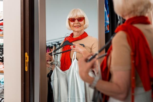 いつまでも若々しい。赤いサングラスをかけ、夏のドレスを手にショッピングミラーを見て、彼女の反射を賞賛しながら、年配のスタイリッシュな女性の腰を上げる