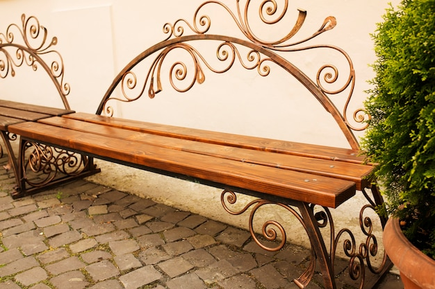 Forged brown wooden bench in the park with cobbles. outdoor shot