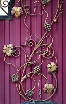 Кованые гроздья винограда. витиеватые кованые элементы украшения металлических ворот.