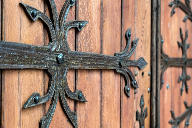 Forged door pattern, decorative. old vintage entrance, massive heavy wooden door of church or cathedral.
