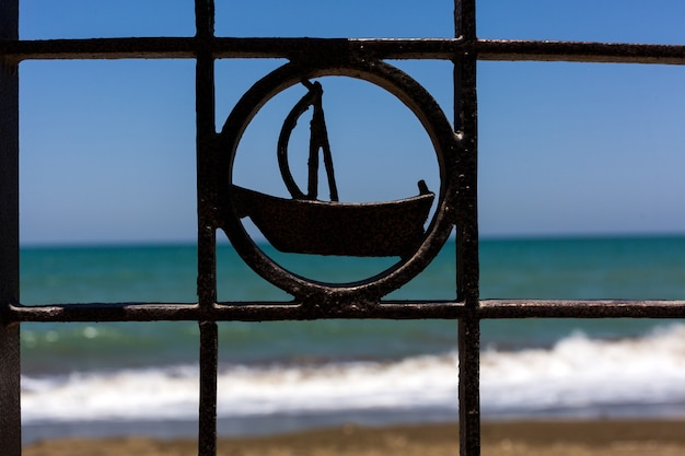 Forged metal fence cage with sail boat sign and sea