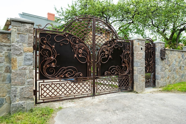 Forged metal gates with patterns and a gate in a stone fence