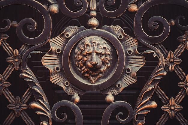 Кованые декоративные детали ворот с чугунной скульптурой в виде головы льва