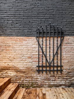 Forged steel metal decorative grille on a brick wall. preservation of vintage items