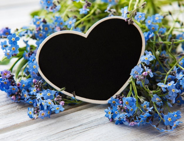 Forget-me-not flowers and black heart shaped board on white wooden background