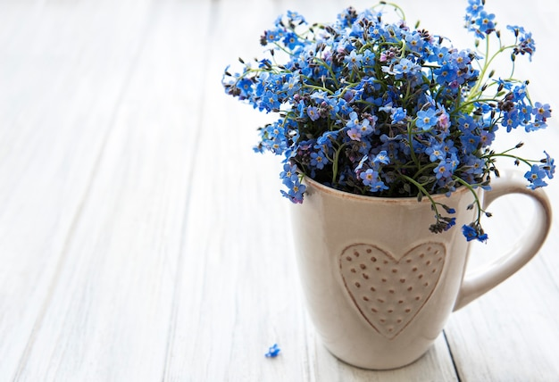 Forget me not flowers in a cup on the table