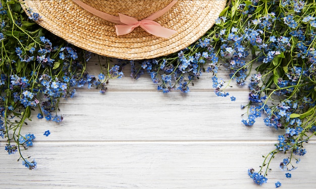 Forget-me-not flowers and straw hat Premium Photo
