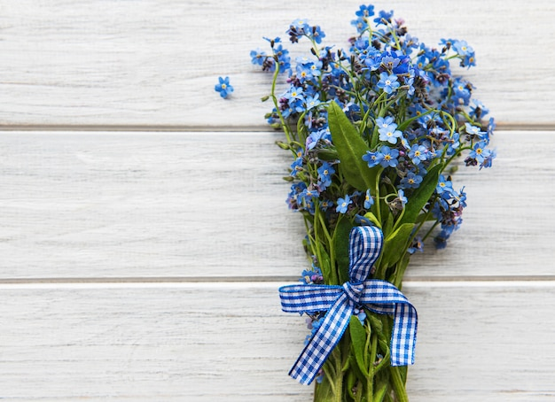 Forget-me-not flowers on a wooden background
