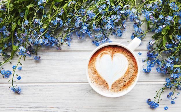 忘れな草の花と木製の背景の上にコーヒーを1杯