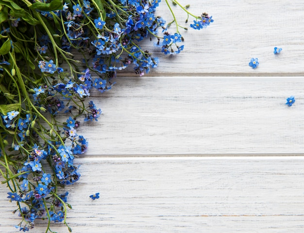 Forget-me-nots on white wooden background with copy space. romance concept.