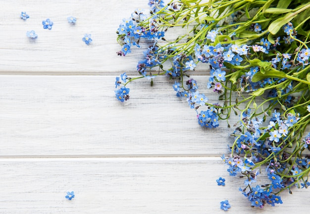 Forget-me-nots on white wooden background