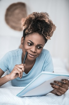 Forget nothing. dark skinned pretty young woman touching cheek with pen lying looking attentively on notepad