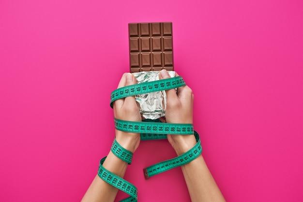 お菓子を忘れて。ピンクの背景に分離されたメジャーテープで包まれた女性の手のチョコレートバー。ダイエットと健康食品のコンセプト