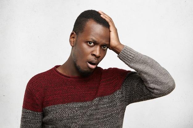忘れっぽくて無知な若いアフリカ系アメリカ人男性は、ショックと欲求不満で口を開けているカジュアルなセーターに身を包み、額に平手打ちをし、結婚記念日を忘れた