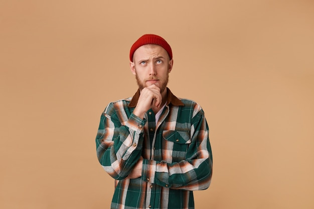 Forgetful confused curious bearded man in checkered shirt and hat, holding fist on chin and with thoughtful clueless expression