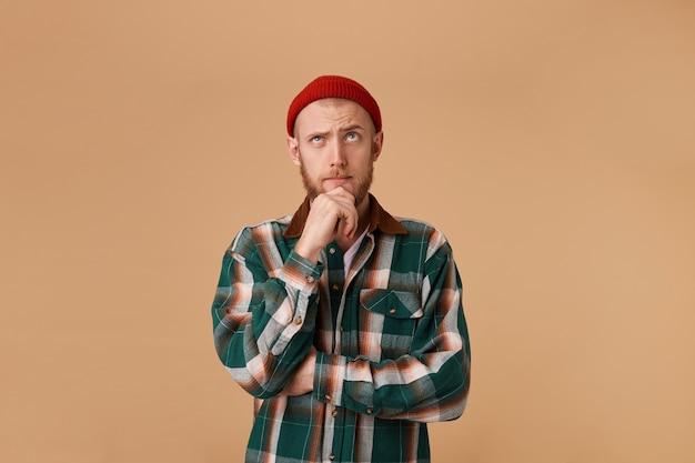 あごに拳を握り、思慮深い無知な表情で、市松模様のシャツと帽子をかぶった忘れっぽい混乱した好奇心旺盛なひげを生やした男