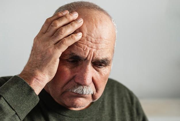 Забывчивый старший мужчина держит руку к голове