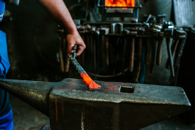 Forging red-hot iron with hammer on anvil.