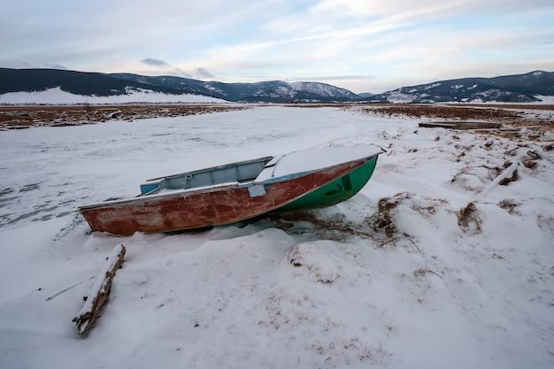 Забытая лодка, замерзшая во льду на реке