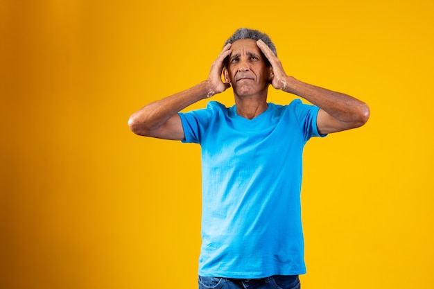 Forgotten and confused elderly afro man on yellow background.