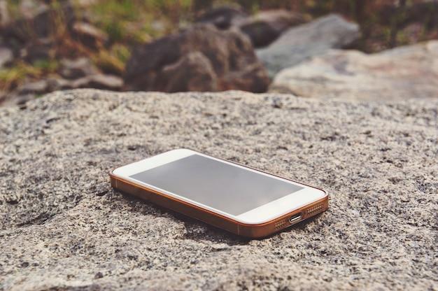 Забытый белый смартфон на скале у побережья. потерян мобильный телефон на берегу озера.