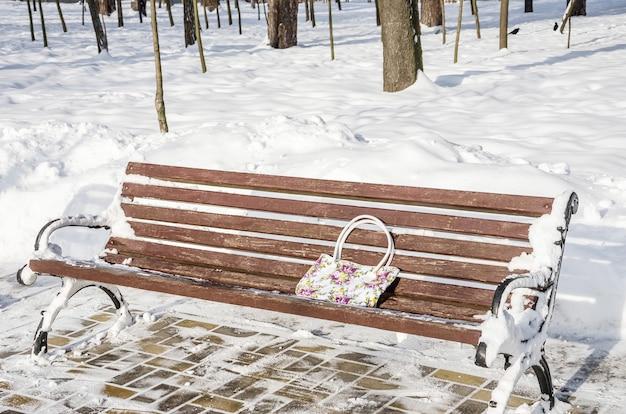 Забытая женская сумка на скамейке в парке