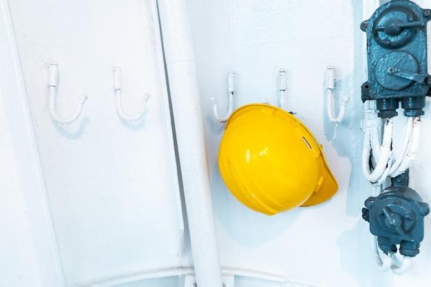Забытый желтый защитный шлем на крючке в раздевалке.