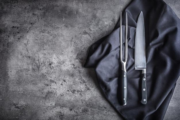 フォークとナイフ。コンクリート板にフォークとナイフの黒いナプキンのテーブルクロス。
