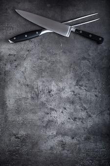 フォークとナイフ。フォークとナイフがコンクリート板の上で交差しました。