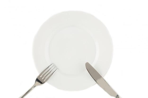 Вилка и нож на белой тарелке
