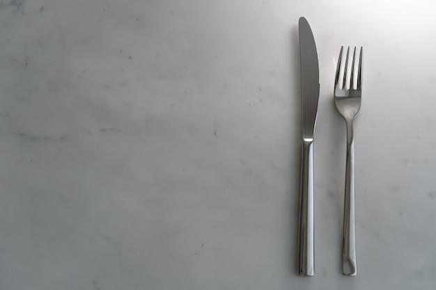 Вилка и нож на фоне белой мраморной текстуры. концепция еды и столовой посуды