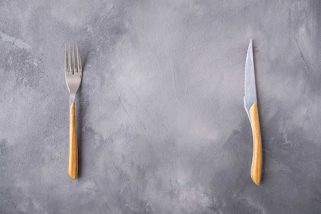 灰色の背景の上のフォークとナイフ..上面図