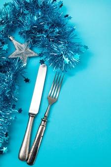 青い背景の上のクリスマスの装飾とフォークとナイフ