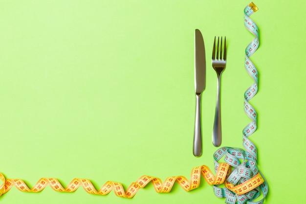 Вилка и нож с свернувшись измерительной ленты на зеленый