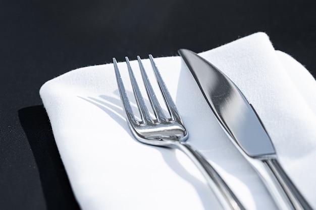 Вилка и нож с белой салфеткой на столе в роскошном ресторане на открытом воздухе изысканное обеденное меню для свадьбы ...