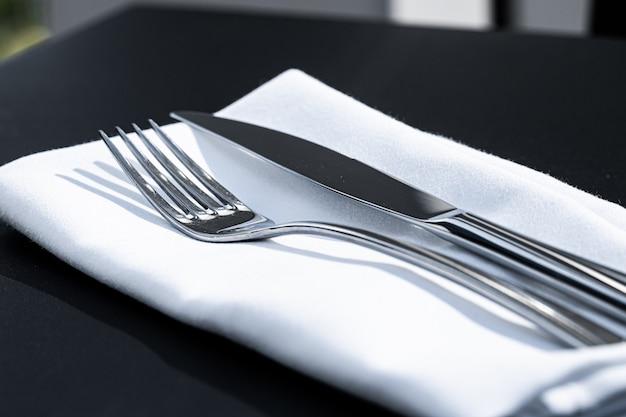 結婚式のための高級レストラン屋外高級ダイニングメニューのテーブルに白いナプキンとフォークとナイフ...