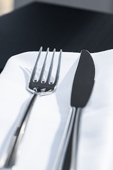 결혼식을 위한 야외 고급 레스토랑의 테이블에 흰색 냅킨이 있는 포크와 나이프...