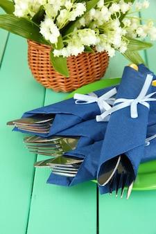 色の木製の背景に青い紙ナプキンで包まれたフォークとナイフ