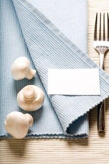 Вилка и грибы на синей салфетке