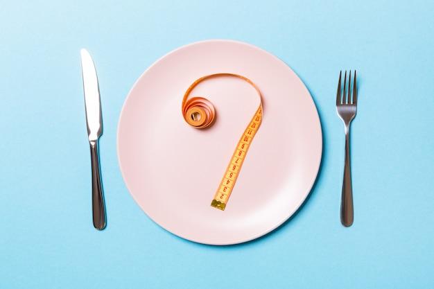 컬러 배경에 테이프를 측정 하여 포크와 접시. 다이어트 개념