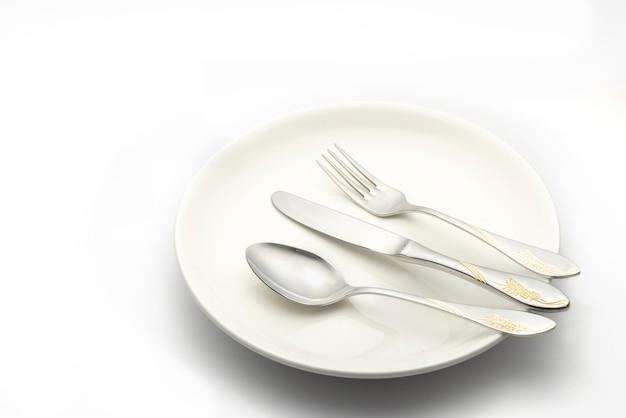 フォークとスプーンを白の白いプレートに置く