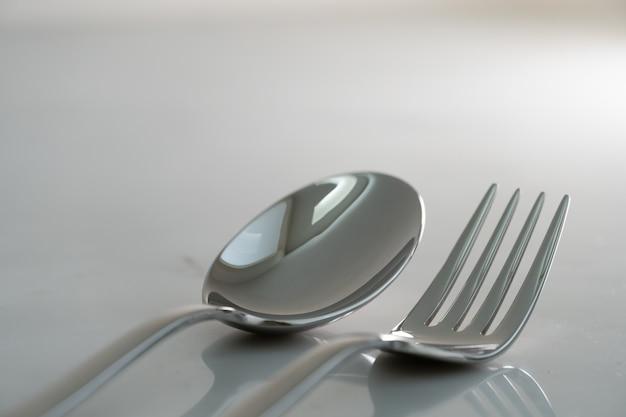 Вилка и ложка на фоне белой мраморной текстуры. концепция еды и столовой посуды