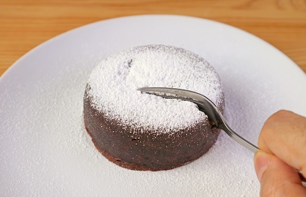 Fork cutting into a delectable rich chocolate cake sprinkled with powdered sugar