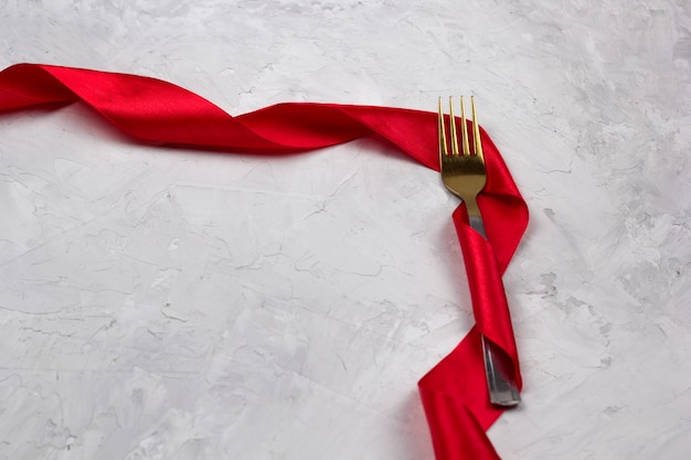 Fork decorated with red satin ribbon for wedding