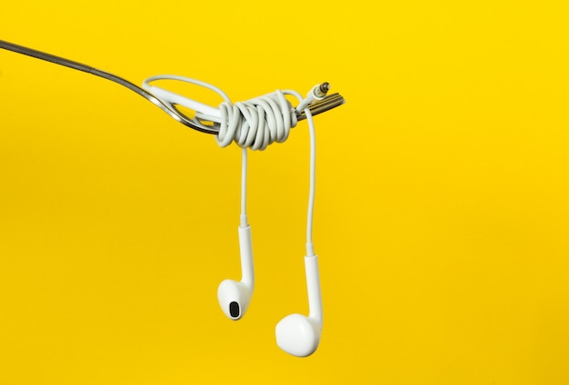 Fork and headphones on a yellow background, close-up