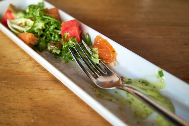 에스카롤 샐러드와 머스타드 소스를 곁들인 절인 연어의 직사각형 흰색 접시에 포크가 나무 테이블에 제공됩니다.