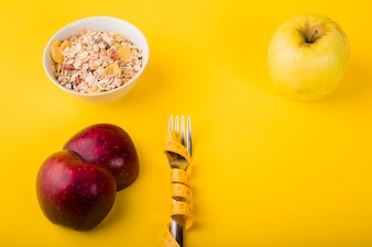 Fork in measuring tape between fruits and bowl of muesli